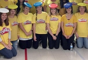 25 people in a group dressed with playdoh shirts and hats